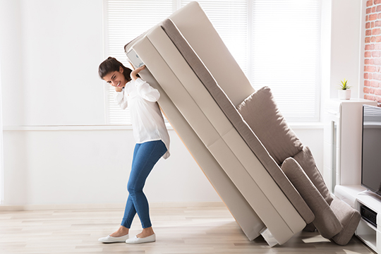 Woman lifting a large sofa